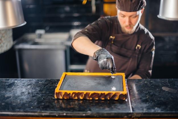 Un chef profesional sirve maravillosamente un jugoso bistec a la parrilla con mantequilla y condimentos. carne a la brasa en un restaurante.