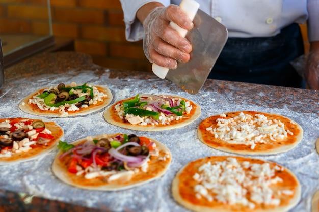 El chef, que pone toppings sobre una pizza.