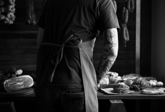 Un chef que trabaja en diferentes tipos de recetas de fotografía de alimentos con carne.