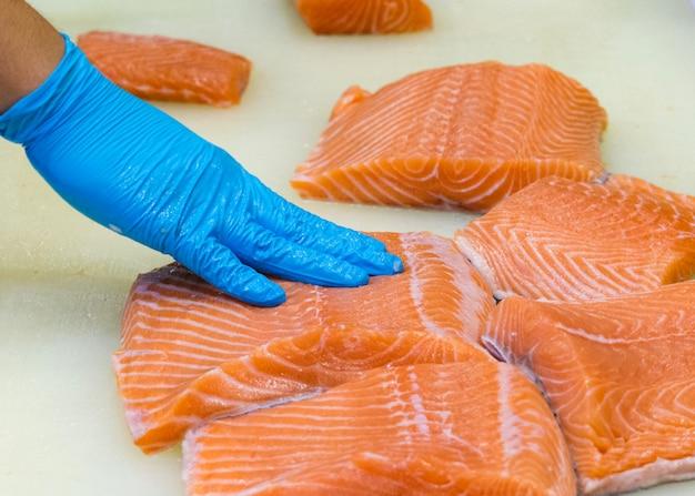 Chef rebanando salmón fresco crudo, chef preparando un salmón fresco en una tabla para cortar