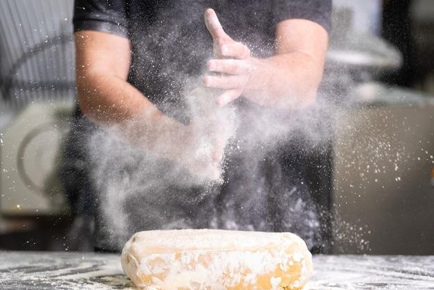 Chef de repostería aplaudiendo sus manos con harina mientras hace masa