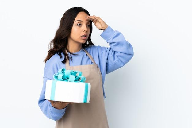 Chef de repostería sosteniendo un gran pastel sobre blanco aislado con expresión de sorpresa mientras mira de lado