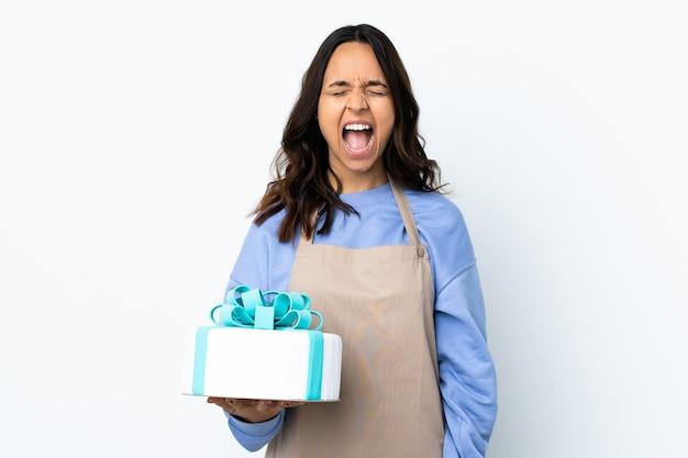 Chef de repostería sosteniendo un gran pastel sobre una pared blanca aislada gritando al frente con la boca abierta