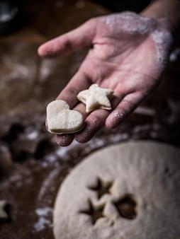 El chef de repostería utiliza moldes de corte para cortar la masa de galletas en la mesa de la cocina.