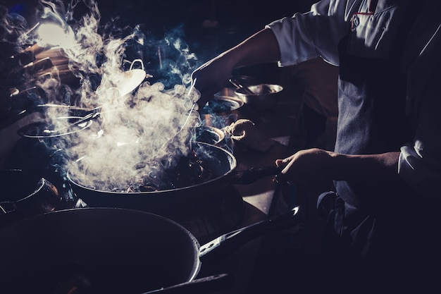 Chef está revolviendo vegetales en wok