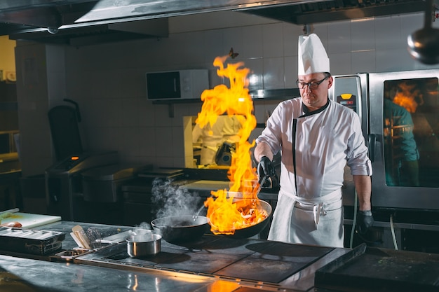 Chef está revolviendo verduras en el wok.