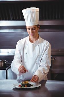Chef rociando especias en el plato