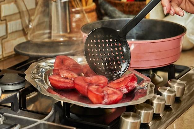 El chef saca peras preparadas cocinadas en almíbar rojo con vino en la estufa de gas.