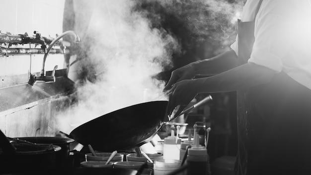 Chef salteado ocupado cocinando en la cocina. chef sofreír la comida en una sartén, fumar y salpicar la salsa en la cocina.