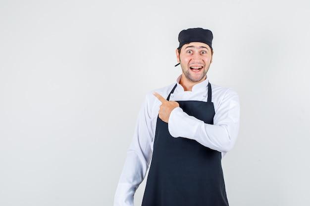 Chef de sexo masculino apuntando hacia atrás en uniforme, delantal y con aspecto alegre. vista frontal.