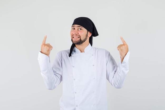 Chef de sexo masculino apuntando con el dedo hacia arriba en uniforme blanco y mirando alegre, vista frontal.