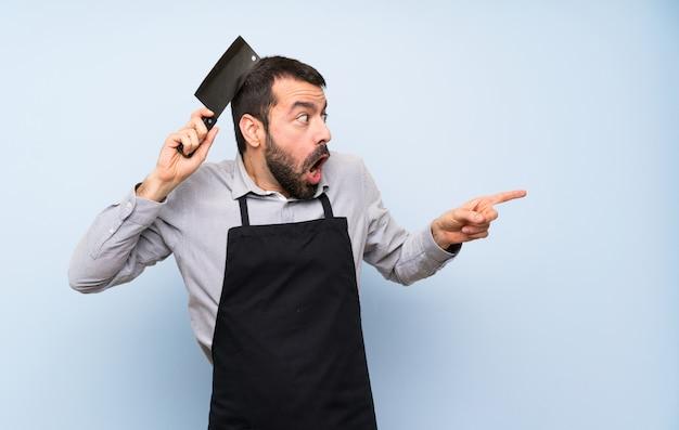 Chef sobre pared azul apuntando hacia el lateral