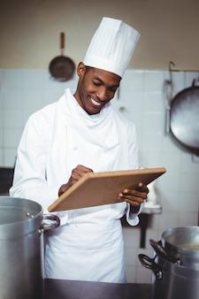 Chef sonriente haciendo notas en un portapapeles