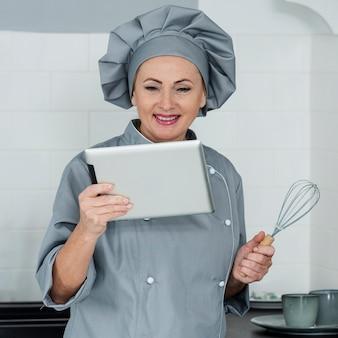 Chef sonriente mirando tableta