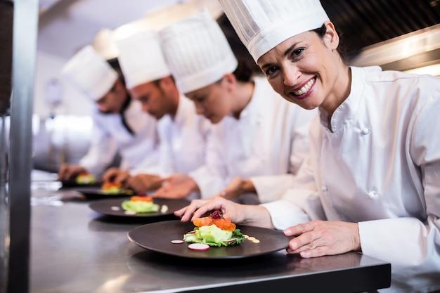 Chef sonriente con plato de comida adornada en la cocina