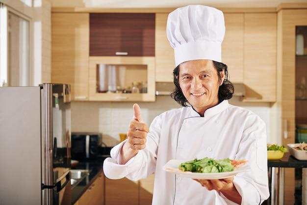 Chef sonriente con plato sabroso