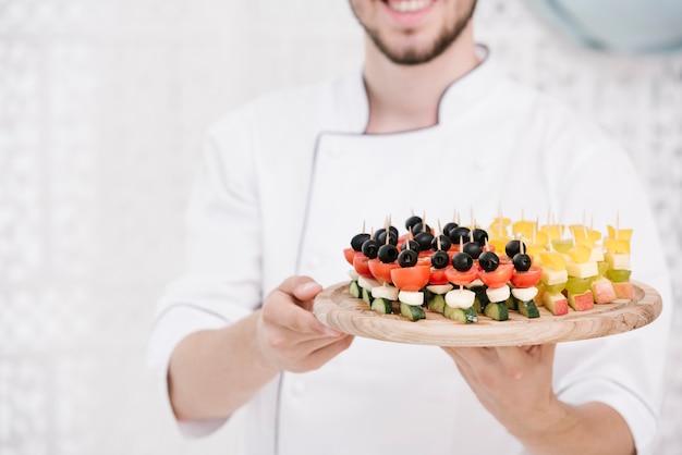 Chef sonriente en uniforme con aperitivos