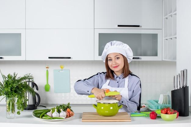 Chef sonriente y verduras frescas con equipo de cocina y tapando la olla en la cocina blanca