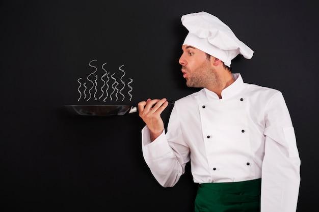 Chef soplando humo de sartén