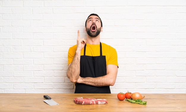 Chef sosteniendo en una cocina apuntando hacia arriba y sorprendido