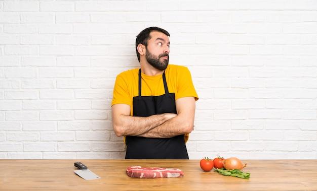 Chef sosteniendo una cocina haciendo gestos de dudas mientras levanta los hombros