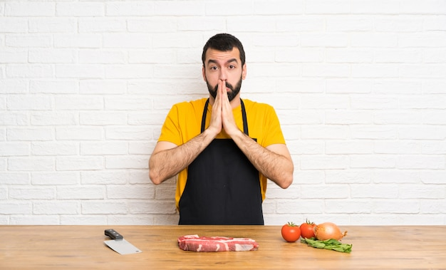 Chef sosteniendo una cocina mantiene la palma unida. la persona pide algo
