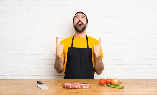 Chef sosteniendo en una cocina sorprendido y apuntando hacia arriba