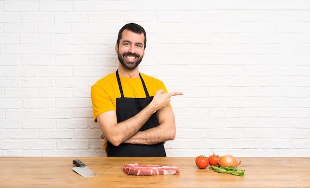 Chef sosteniendo en un dedo señalador de cocina a un lado