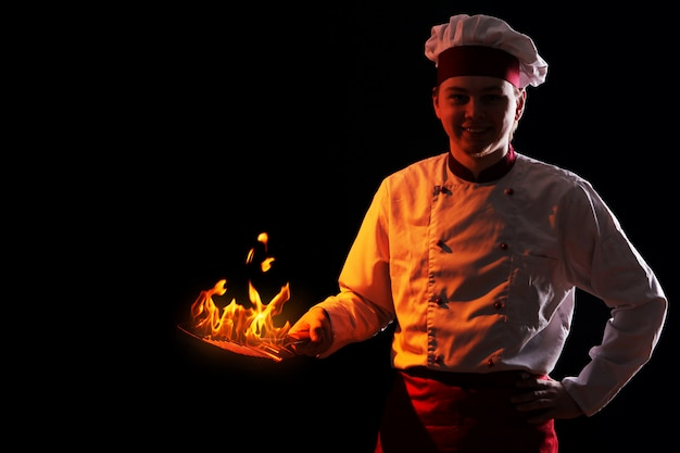 Chef sosteniendo pan con fuego dentro