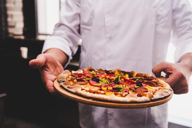 Chef sosteniendo un plato de madera con una deliciosa pizza en la cocina