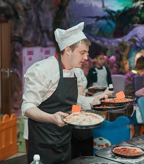 El chef sostiene una pizza recién preparada. comida deliciosa