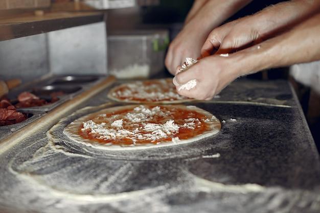 Chef en uniforme blanco prepara una pizzaa