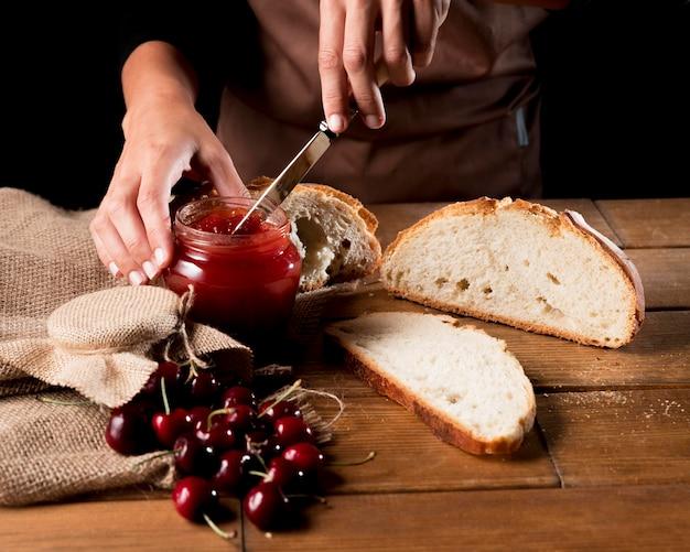 Chef untando mermelada de cerezas en pan