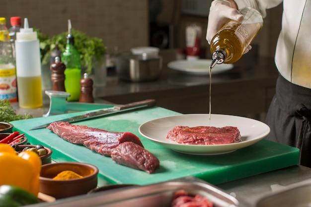 Chef vertiendo aceite de oliva de la botella en la pieza de carne en el plato