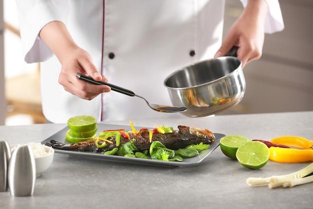 Chef vertiendo pescado con deliciosa salsa en restaurante.