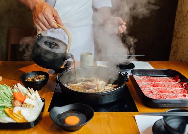 El chef vierte salsa de soya en vegetales salteados como la cebolla