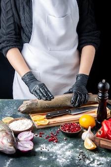 Chef de vista frontal en delantal blanco para picar pescado crudo en tablero de madera molinillo de pimienta tazón de harina semillas de granada en un tazón en la mesa de la cocina