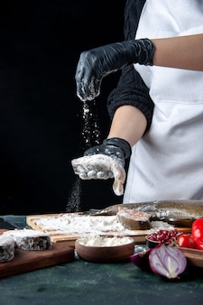 Chef de vista frontal que cubre rodajas de pescado crudo con harina en la mesa de la cocina
