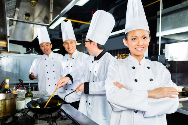 Chefs asiáticos en la cocina del restaurante del hotel.