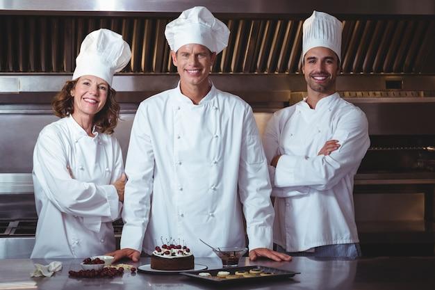 Chefs felices y orgullosos de presentar el pastel que acaban de hacer