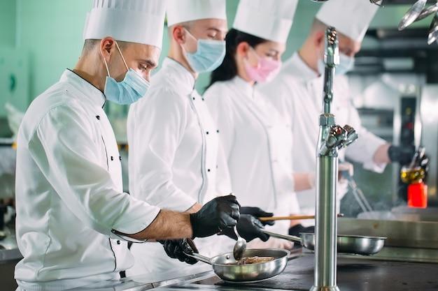 Los chefs con máscaras protectoras y guantes preparan la comida en la cocina de un restaurante u hotel.