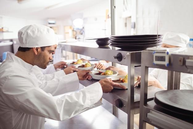 Chefs pasando comida preparada al camarero en la estación de pedidos