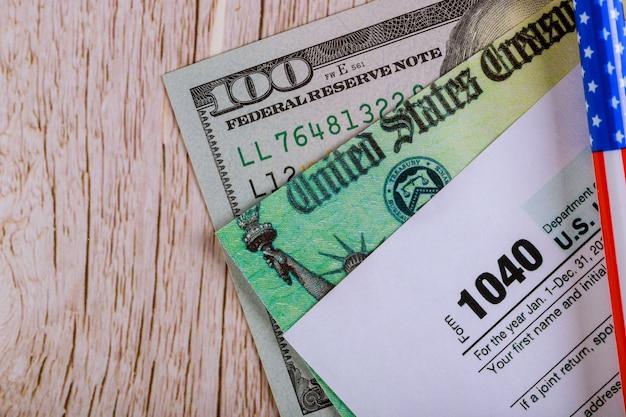 Cheque de declaración de impuestos económicos de estímulo y billetes de 100 dólares estadounidenses