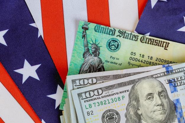 Cheque de declaración de impuestos económicos de estímulo y moneda de billetes de 100 dólares estadounidenses con bandera estadounidense