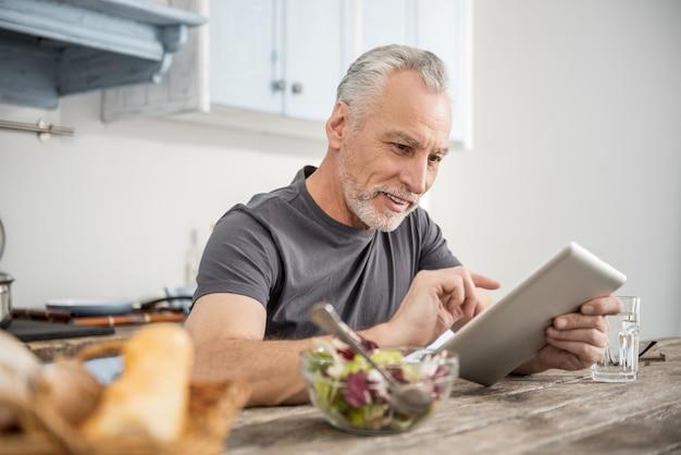 Chequeo por correo. pensionista encantado positivo sentado en la cocina y apoyado en la mesa mientras mira su tableta