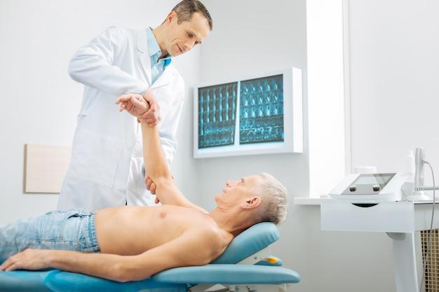 Chequeo de músculos. agradable agradable anciano levantando el brazo y mirando a su terapeuta mientras está acostado en la cama médica