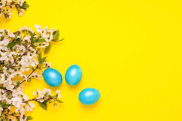 Cherry blossom branch y easter blue eggs en el fondo amarillo.