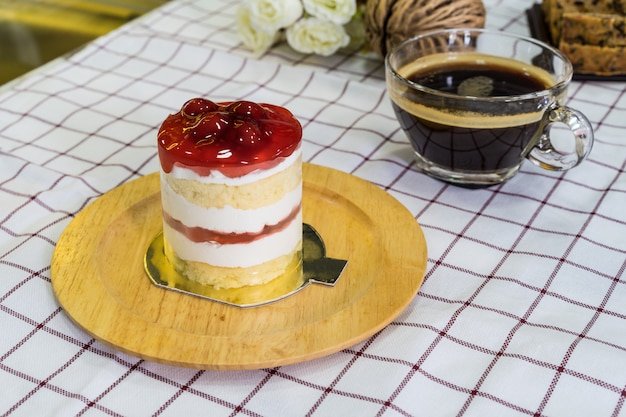 Cherry cream cake en plato de madera y taza de café