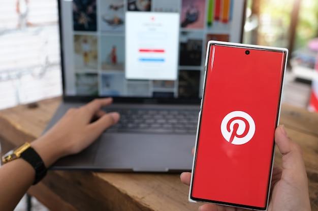 Chiangmai, tailandia - 06 de junio de 2021: mano de mujer sosteniendo el teléfono inteligente móvil con la aplicación de pinterest en la pantalla. pinterest es un tablón de anuncios en línea que permite a las personas marcar sus cosas interesantes.