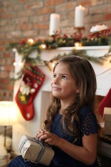 Chica abriendo caja de regalo de navidad